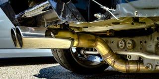 在汽车的底部的双重镀铬物排气管 免版税库存照片
