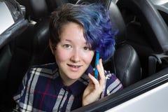 在汽车的微笑的十几岁的女孩就座,当谈话在手机时 库存图片