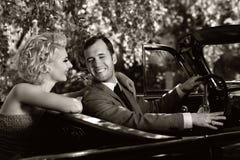 在汽车的微笑的夫妇 免版税库存图片