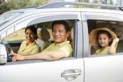 在汽车的快乐的家庭骑马 图库摄影