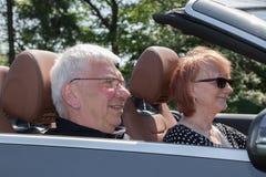 在汽车的愉快的资深夫妇在一个晴天 库存照片