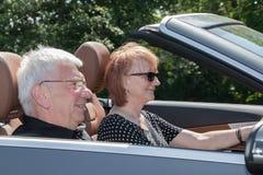在汽车的愉快的资深夫妇在一个晴天 免版税库存图片