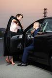 在汽车的愉快的年轻企业夫妇 库存照片