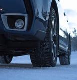 在汽车的散布的防滑轮胎在冬天路特写镜头 免版税库存图片