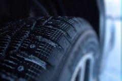 在汽车的散布的防滑轮胎在冬天路特写镜头 库存图片