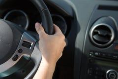 在汽车的方向盘的手 免版税库存图片