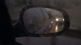 在汽车的旁边镜子的雨珠,特写镜头 股票录像