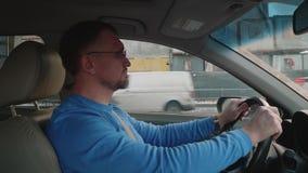 在汽车的白色司机在建筑前面 汽车在等待绿色红灯的交叉路 影视素材