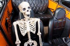 在汽车的笑的骨骼 库存照片