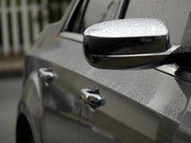 在汽车的边的小雨下落 免版税库存照片