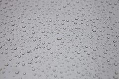在汽车的雨下落 免版税库存图片