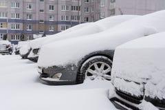 在汽车的雪在降雪以后 冬天都市场面 免版税库存照片