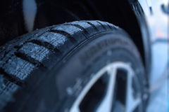 在汽车的非散布的防滑轮胎在冬天路特写镜头 库存照片