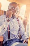 在汽车的非洲商人发表演讲关于智能手机 免版税库存图片