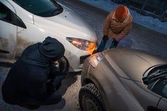 在汽车碰撞以后的两个司机在冬天街道上 库存照片