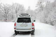 在汽车路多雪的无法认出的冬天之后 库存图片