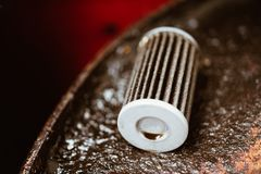 在汽车车库的老润滑剂发动机润滑油滤清器 免版税库存图片