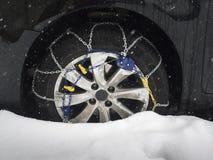在汽车轮胎的雪链子在雪 库存照片