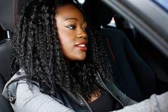 在汽车里面的凉快的年轻黑人妇女 免版税图库摄影