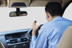 在汽车里面的恼怒的年轻人 免版税库存照片