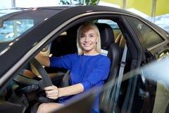 在汽车里面的愉快的妇女在车展或沙龙 免版税库存照片