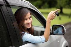 在汽车里面的年轻亚裔妇女,把握关键从窗口 免版税库存照片