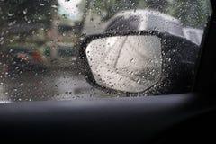 在汽车镜子的雨 免版税库存照片