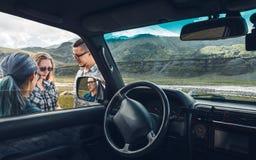 在汽车附近的三个朋友在旅途谈论路线 旅行假期概念 免版税库存图片