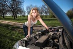 在汽车附近的女孩有一个开放敞篷的 免版税库存图片