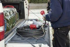 在汽车附近的工作者有建筑工作的力量extander电子插座的与红色插口在他的手上 免版税库存图片