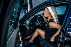 在汽车附近的白肤金发的女实业家在城市 免版税库存图片