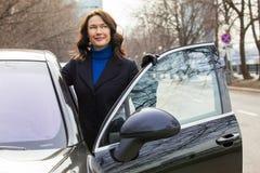 在汽车附近的美丽的女实业家 免版税库存图片