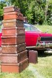 在汽车附近的老手提箱 免版税库存照片
