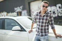 在汽车附近的英俊的人 白兰地酒企业雪茄玻璃寿命豪华人纵向 库存图片
