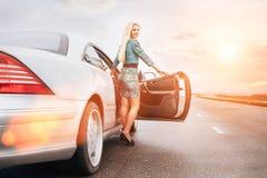在汽车附近的年轻白肤金发的妇女逗留在偏僻的高速公路 库存照片