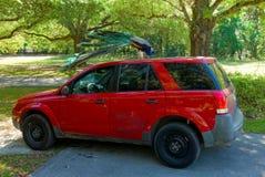 在汽车顶部的一个孔雀 图库摄影