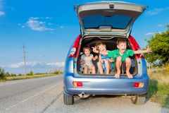 在汽车,家庭旅行,暑假旅行的愉快的孩子 库存照片