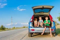 在汽车,家庭旅行,暑假旅行的愉快的孩子 免版税库存照片
