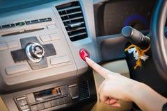 在汽车仪表板的女性手紧迫应急灯按钮 图库摄影