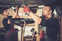 在汽车engi的专业汽车修理师改变的机油 免版税库存图片