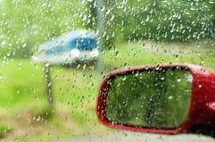 在汽车widnow的被聚焦的雨下落与一列以后的火车在背景 库存图片