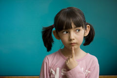 在沉思学校女小学生逗留附近的黑板 免版税库存照片