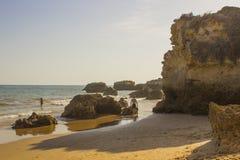在沉淀沙子下的假日制造商在Albuferia向在普腊亚da Oura海滩的峭壁面孔扔石头 库存照片