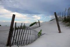 在沙丘和俏丽的天空埋没的篱芭 免版税库存图片