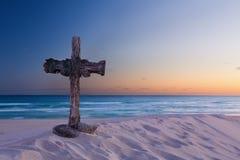 在沙丘的一个老十字架在有镇静日出的海洋旁边 免版税库存图片