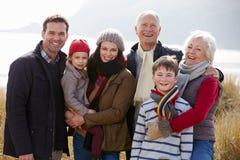 在沙丘的多一代家庭在冬天海滩 免版税图库摄影