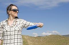 在沙丘的妇女投掷的飞碟 免版税库存照片