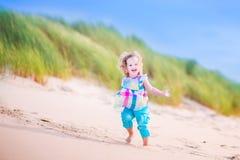 在沙丘的小女孩runnign 免版税库存照片