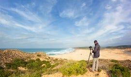 在沙丘的男性摄影师旅行和摄影。 库存照片