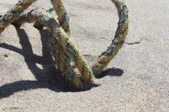 在沙丘的老被风化的钓鱼的绳索在含沙沿海海洋海滩 图库摄影